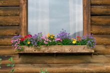 Rustic Wood Cabin With Colorful Flowers In The Windowbox
