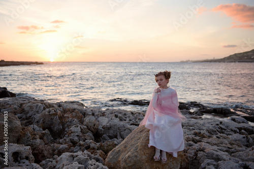 Valokuva  pensive sad princess girl in a pink dress and a diadem is sitting on a rock on t