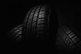 New and unused car tires against dark background