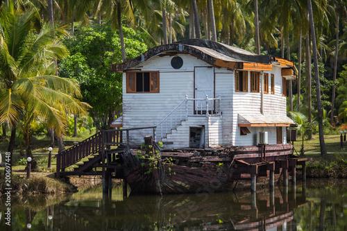 Foto op Canvas Schipbreuk Abandoned dock or ship house in the Asian jungle.