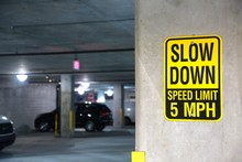 Yellow And Black Slow Down Speed Limit 5 Mph Sign In A Parking Garage With Cars Out Of Focus In The Background