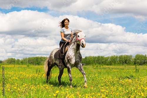 Fotografie, Tablou Woman riding on grey horse in the field