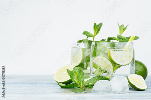 Papiers peints Cocktail Tropical fresh cold cocktail gin tonic with mint, lime, ice, straw on light blue shabby wood board and white background, copy space.