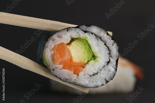 Fototapeta Close up of chop sticks holding a salmon avocado maki sushi obraz