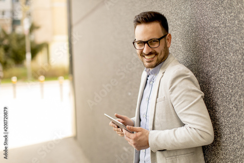 Fotografia  Young businessman with digital tablet by the grey wall