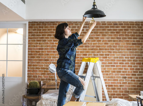 Woman changing lightbulb Wallpaper Mural