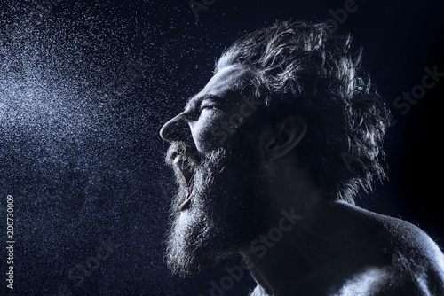 Stampa su Tela A bearded man angrily screams into a spray of water against a black background