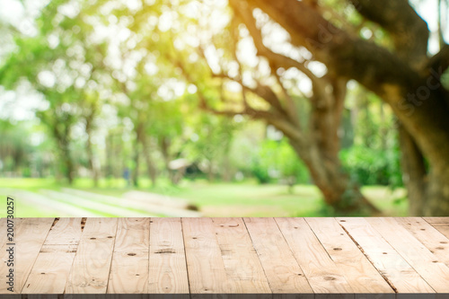 Papiers peints Jardin Empty wood table and defocused bokeh and blur background of garden trees in sunlight, display montage for product.