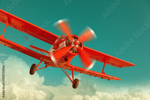Red biplane flying in the cloudy sky. Retro style Canvas Print
