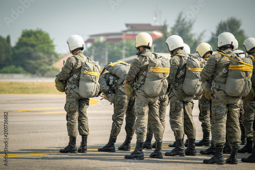 Photo row of paratrooper in camouflage uniform hold T-10 static line hook and parachut