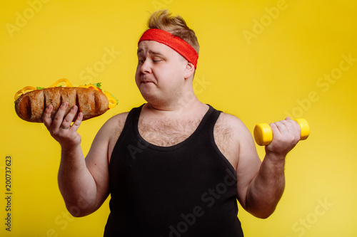 Fotografia  Fat sportsman has ruined the diet with yummy humburger. Gluttony.