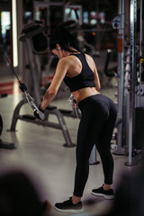 rear view of woman exercising power cable crossover for chest muscles at gym