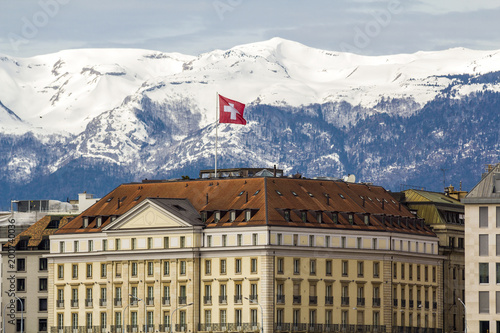 Carta da parati Facades of historic buildings in the city center of Geneva, Switzerland on the Leman lake with snow covered Alps mountains peaks in sunny clear day