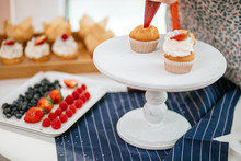 Strawberry Filled Cupcakes With Creamy Frosting On White Serving Platter, Cupcakes And Berries On The Background