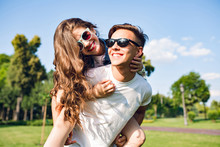 Pretty Girl With Long Curly Hair Is Riding On Back Of Handsome Guy In Park. They Wear Sunglasses And Have Fun.