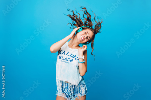 Fotografiet  Energy girl with blue headphones  listening to music with closed eyes  on blue background in studio