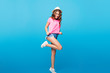 Attractive girl with long curly hair in hat jumping on blue background in studio. She wears shorts, pink T-shirt. She pulls on down T-shirt and looks to camera.