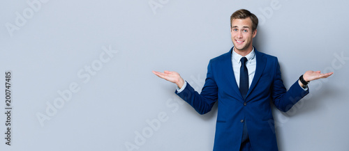 Fotografie, Obraz  Smiling businessman showing something or copyspace