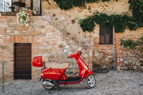 In the courtyard of an old house in Italy there is a red scooter Slika na platnu