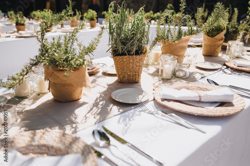 Foto op Aluminium Buffet, Bar on festive table in wedding banquet area are plates, glasses, candles, cutlery, the table is decorated with compositions from greens and napkins