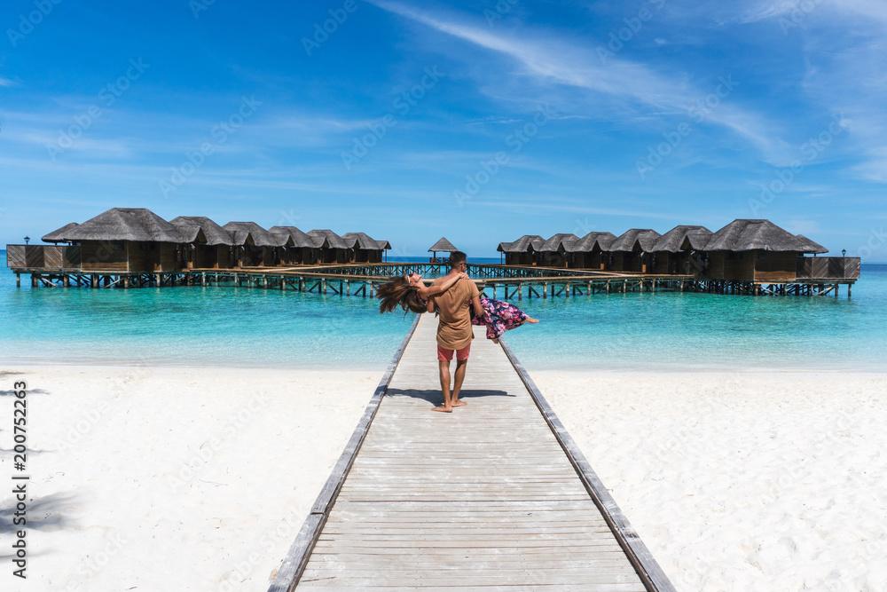 Fototapeta Honeymoon on Maldives. Man holding his wife on arms on bridge on ocean beach
