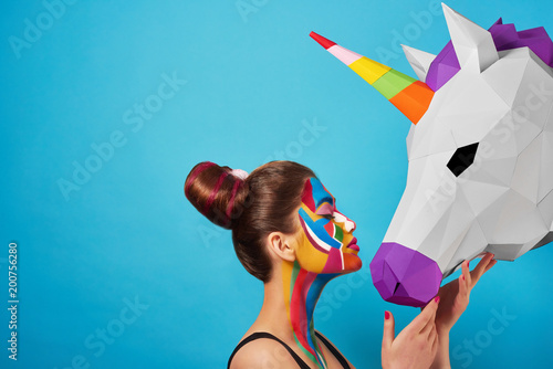 Pop Art Sideview of pop art portrait of model wearing black opened top. Girl has saturated make up with bright geometrical figures and fancy hairdress. Posing on blue background with pink paper unicorn's head