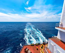 Panoramic View On Trail On Sea Surface Behind Cargo Ship At Sea In Beautiful Sunny Day