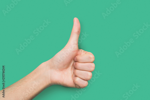 Male hand making thumb up gesture isolated on green Wallpaper Mural