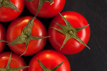 Top view - Cherry tomatoes on dark background. Vegetarian or vegan menu design. Place for text