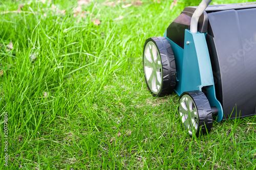 Fotografie, Obraz  Scarifier on green grass. Work in the garden. scarifier