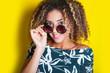 Leinwandbild Motiv portrait of a young afro american woman in sunglasses. Yellow background. Lifestyle.