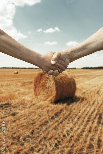 Photo Farmers handshake with wheat field in harvest time on background