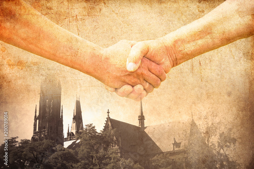 Obraz handshake of two conflict people with Church on background - fototapety do salonu