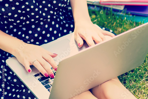 Papiers peints Akt Top view of woman sitting in park on the green grass with laptop, notebook and smartphone, hands on keyboard. Computer screen mockup. Student studying outdoors. Copy space for text