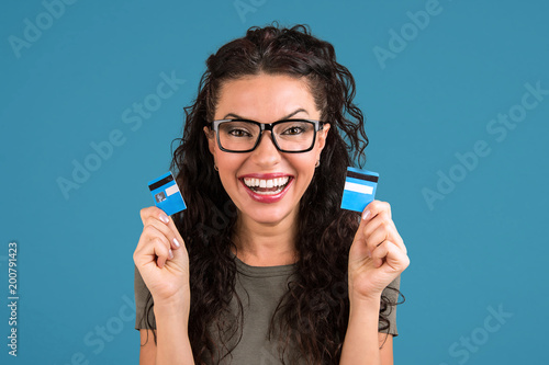 Fotografie, Tablou Happy debt free woman holding a credit card cut in two pieces