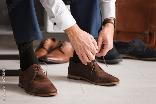 Man trying on new shoes indoors, closeup