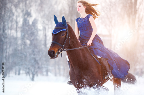 Young girl in blue dress galloping horseback on winter field Canvas Print
