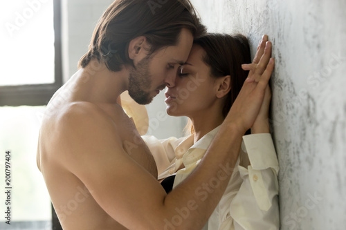 Beautiful young sensual couple holding hands leaning on wall, loving millennial Wallpaper Mural