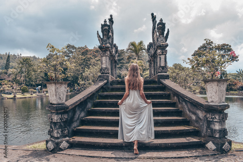Staande foto Bleke violet beautiful girl with long dark hair in elegant grey dress posing in Tirta Gangga water temple in Bali
