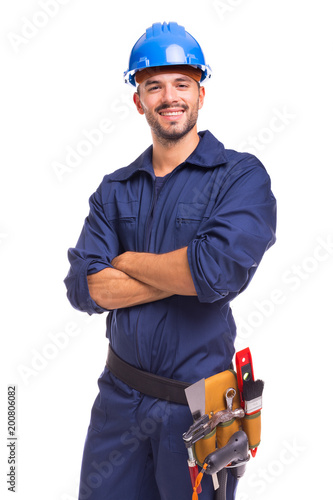 Slika na platnu Portrait of a confident young worker standing with arms crossed on white backgro