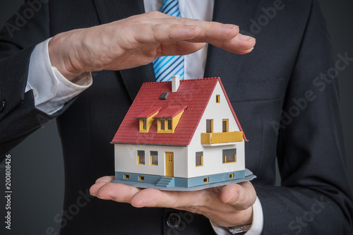Papiers peints Akt Home insurance concept. Man is holding model of house.