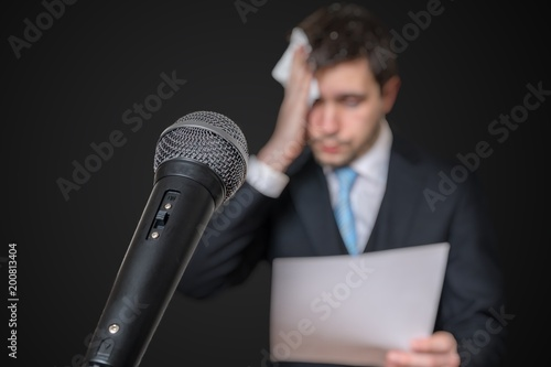 Microphone in front of a nervous man who is afraid of public speech and sweating.