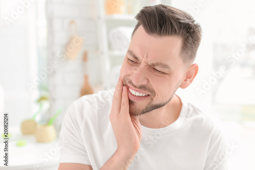 Fotografia  Young man suffering from toothache indoors