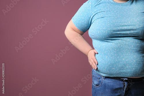 Obraz na plátne  Overweight woman on color background