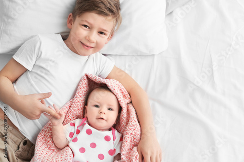 Valokuva  Cute little baby with elder brother lying on bed at home