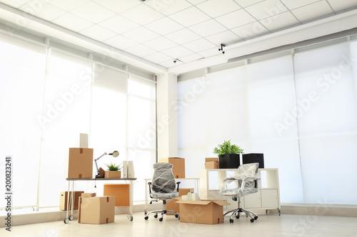 Fototapeta Moving boxes and furniture in new office obraz na płótnie