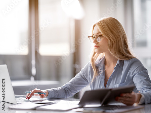 Fotografie, Obraz  Serious blond girl typing on laptop while holding notebook