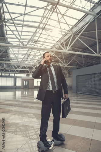 Papiers peints Retro Full length portrait of focused bearded businessman communicating by phone while moving on gyroboard in warehouse. He keeping suitcase in hand. Undistracted worker using gadgets during labor concept