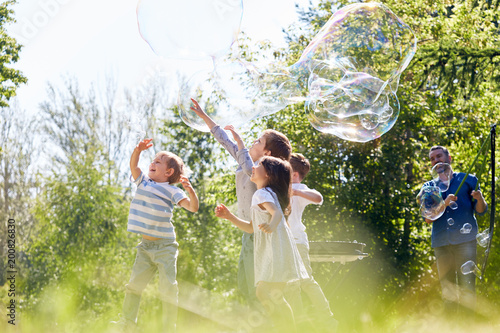 Fotomural  Profile view of little friends having fun while participating in soap bubble sho