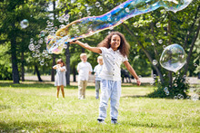 Adorable African American Girl Making Soap Bubbles While Her Little Friends Standing Behind Her And Keeping Eye On Her, Sunny Public Park On Background